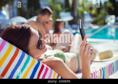 Woman sunbathing and texting by swimming pool - Stock Photo