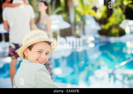Portrait of smiling boy wearing sun hat sitting by swimming pool - Stock Photo