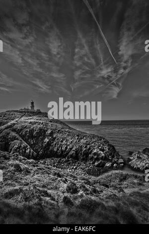 A black and white photograph of a landscape incorporating a lighthouse shot in Pembroke, Wales, UK - Stock Photo