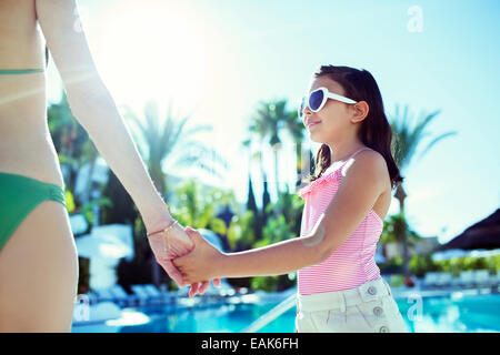 Mother and daughter holding hands by swimming pool - Stock Photo