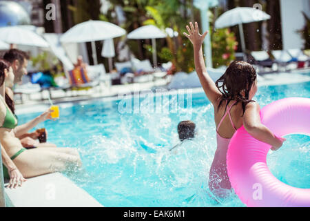 Girl with pink inflatable ring jumping into swimming pool, family in background - Stock Photo