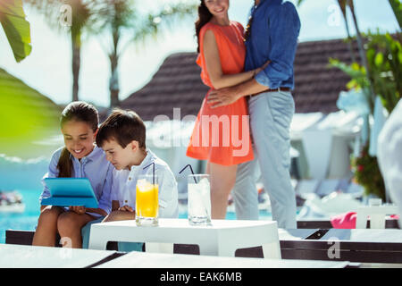 Brother and sister using digital tablet by resort swimming pool, parents embracing in background - Stock Photo