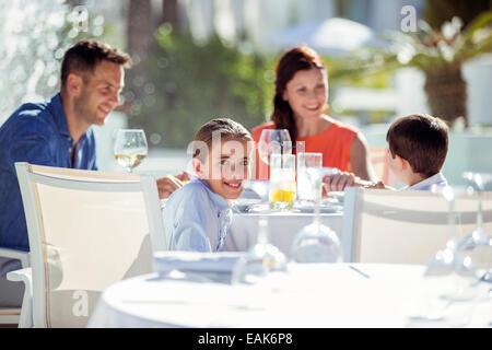 Family with two children having dinner in resort outdoors - Stock Photo