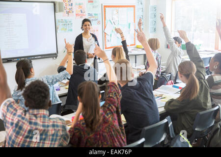 Rear view of teenage students raising hands in classroom - Stock Photo