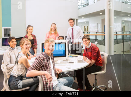 Group portrait of teenage students with their teacher at table - Stock Photo