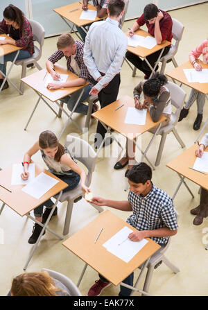 Overhead view of students passing note between desks during their GCSE exam - Stock Photo
