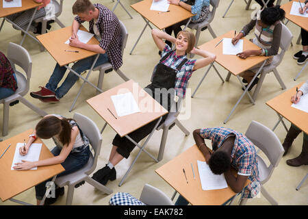 Students writing their GCSE exam in classroom - Stock Photo
