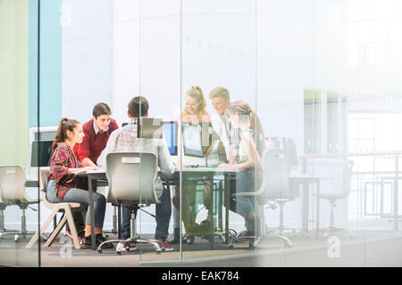 Students working with computers behind glass door - Stock Photo