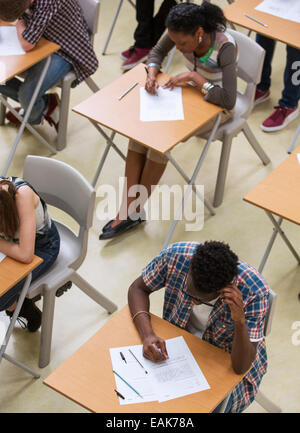 Elevated view of students writing their GCSE exam in classroom - Stock Photo