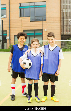 Portrait of three smiling boys wearing soccer uniforms and holding soccer ball in front of school - Stock Photo