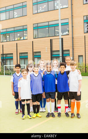 Group portrait of children wearing sport uniforms standing in front of school - Stock Photo