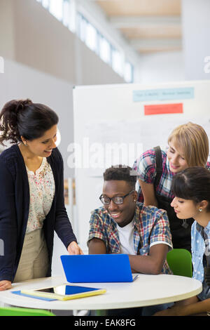 Students and teacher working with laptop - Stock Photo