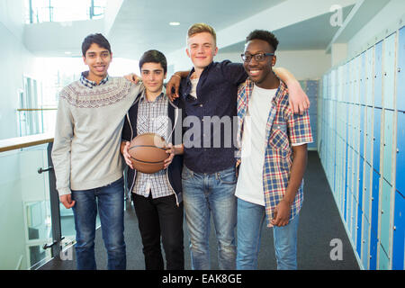 Group portrait of male students holding basketball in school corridor - Stock Photo