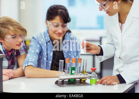 Teacher and students during chemistry lesson, wearing protective eyewear and looking at test tubes - Stock Photo