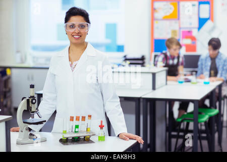 Portrait of smiling female teacher wearing protective eyewear, standing behind desk microscope and test tubes in - Stock Photo