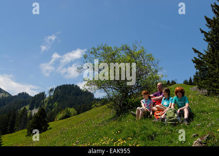 Hikers, father, 45, daughters, 11, son, 13, resting on the Kappeler Alp, Nesselwang, Swabia, Bavaria, Germany - Stock Photo