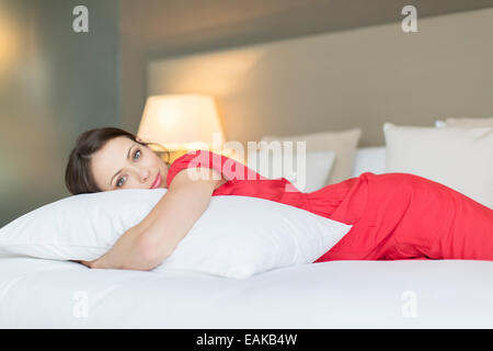 Portrait of beautiful woman wearing red dress lying on bed and hugging pillow - Stock Photo
