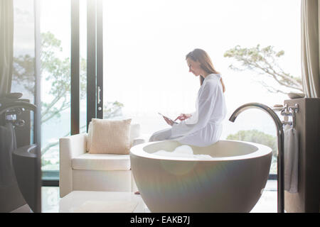 Woman wearing white bathrobe sitting on edge of modern bathtub and using digital tablet - Stock Photo