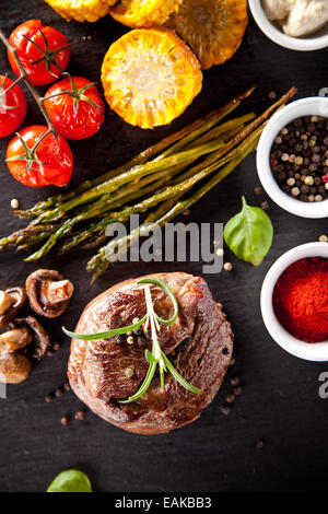 Piece of red meat steak with vegetable, herbs and spices, served on black stone surface. Shot from top view - Stock Photo