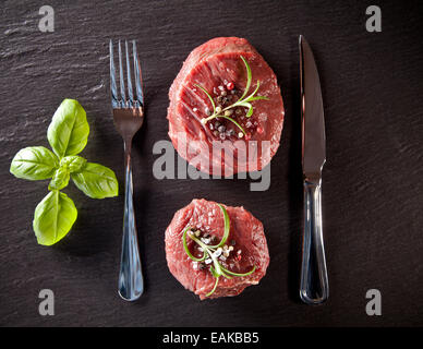 Pieces of red raw meat steaks with herbs, served on black stone surface. Shot from upper view. - Stock Photo