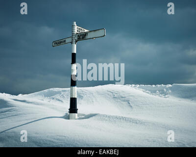 photograph of buried road sign on top of hill covered in large snow drift between Frodsham, Kingsley and Helsby - Stock Photo