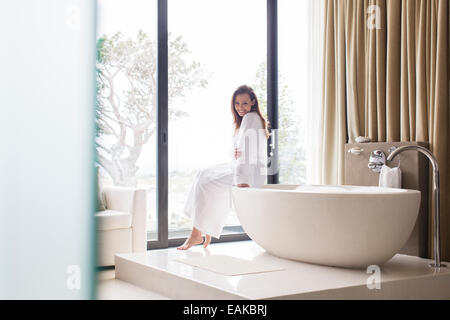 Portrait of smiling woman wearing white bathrobe, sitting on edge of bathtub in bathroom - Stock Photo