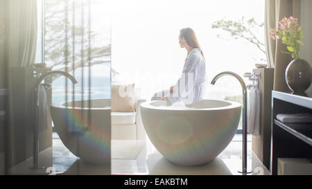 Woman wearing white bathrobe, sitting on edge of bathtub and looking through window - Stock Photo