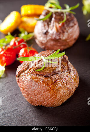 Beef steak served with grilled vegetable and herbs on black stone table - Stock Photo