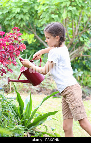 Girl watering plants in garden with red watering can - Stock Photo
