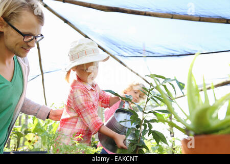 Man assisting girl watering plants with watering can in greenhouse, boy in background - Stock Photo