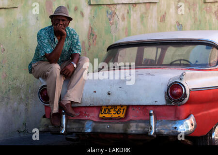Cuban taxi driver with his vintage taxi, Santiago de Cuba, Cuba - Stock Photo
