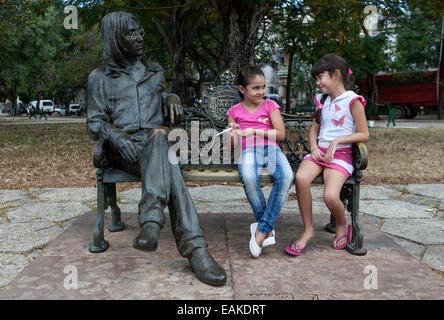 Two girls sitting on a bench next to a bronze sculpture of John Lennon, Havana, Cuba - Stock Photo