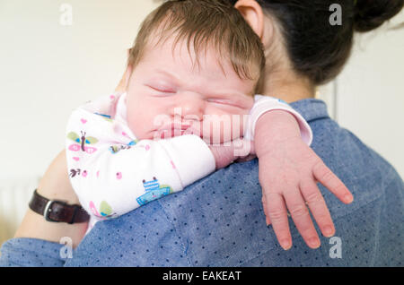 One week old newborn baby girl asleep on mothers shoulder - Stock Photo