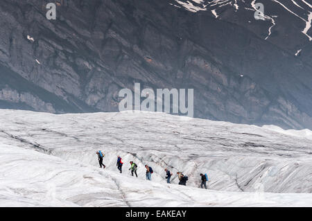 Aerial of hikers waling on a glacier at Wrangell St. Elias National Park in Alaska. - Stock Photo