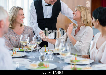 Waiter offering wine to female client at restaurant table, woman refusing - Stock Photo