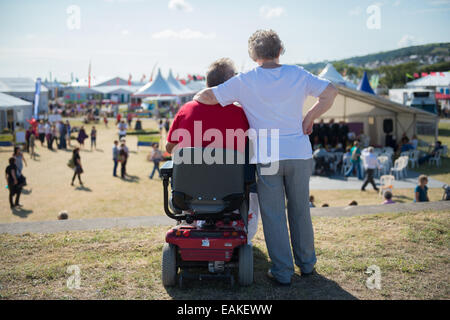 Disability Access:  A disabled, wheelchair-using,  man with his wife at the National Eisteddfod of Wales 2014 - Stock Photo