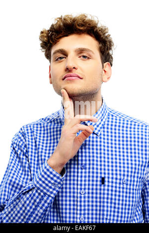 Young casual man touching his chin over white background - Stock Photo
