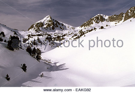 Snowshoeing men and Bastan peak, Hautes-Pyrenees, France. - Stock Photo