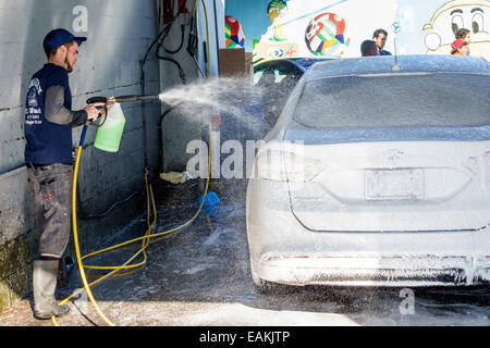 Miami Florida Little Havana car wash Hispanic man working washing high power washer wand soap cleaning - Stock Photo