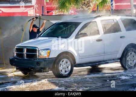 Miami Florida Little Havana car wash Hispanic man working washing cleaning high power washer wand SUV - Stock Photo