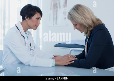 Female doctor consoling sad woman at desk in office - Stock Photo