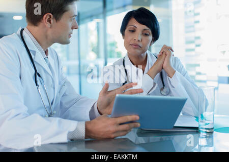Doctors discussing patient's treatment at desk, using digital tablet - Stock Photo