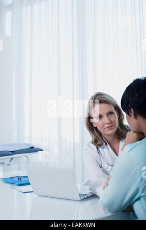 Female doctor talking to woman at desk in office - Stock Photo