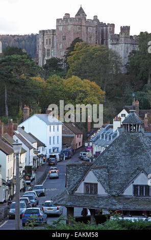 View of the 11th century Dunster Castle looking up the village High Street, with the 17th century Yarn Market in - Stock Photo