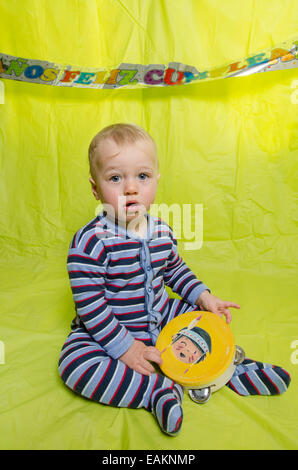 A baby boy (12 months old) with a tambourine. - Stock Photo