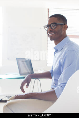 Portrait of young smiling man wearing glasses and blue shirt sitting at desk with laptop - Stock Photo