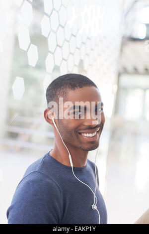 Portrait of smiling young man with earphones in office - Stock Photo