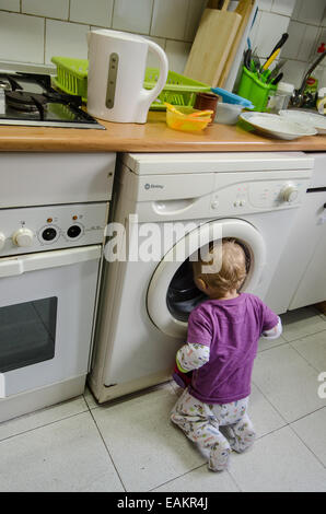 A baby boy (ca. 18 months old) watches laundry being washed in a washing machine. - Stock Photo