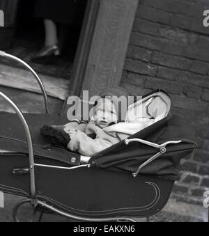 1950s historical picture showing a young child sitting up in a traditional pram in the street outside a front door - Stock Photo