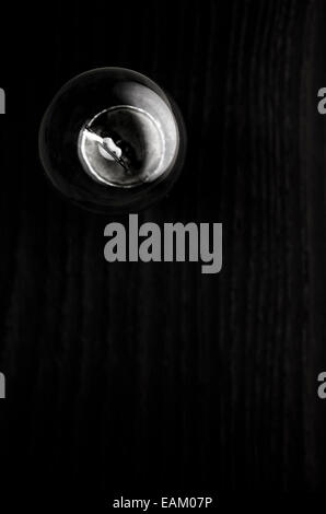 light bulb on a wood surface, black and white - Stock Photo